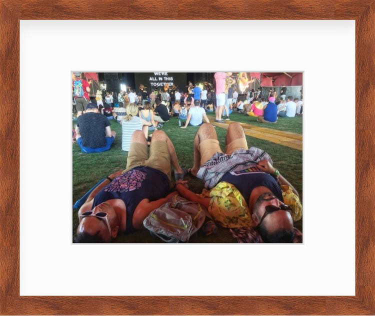 Men laying in field at music festival in a wood frame