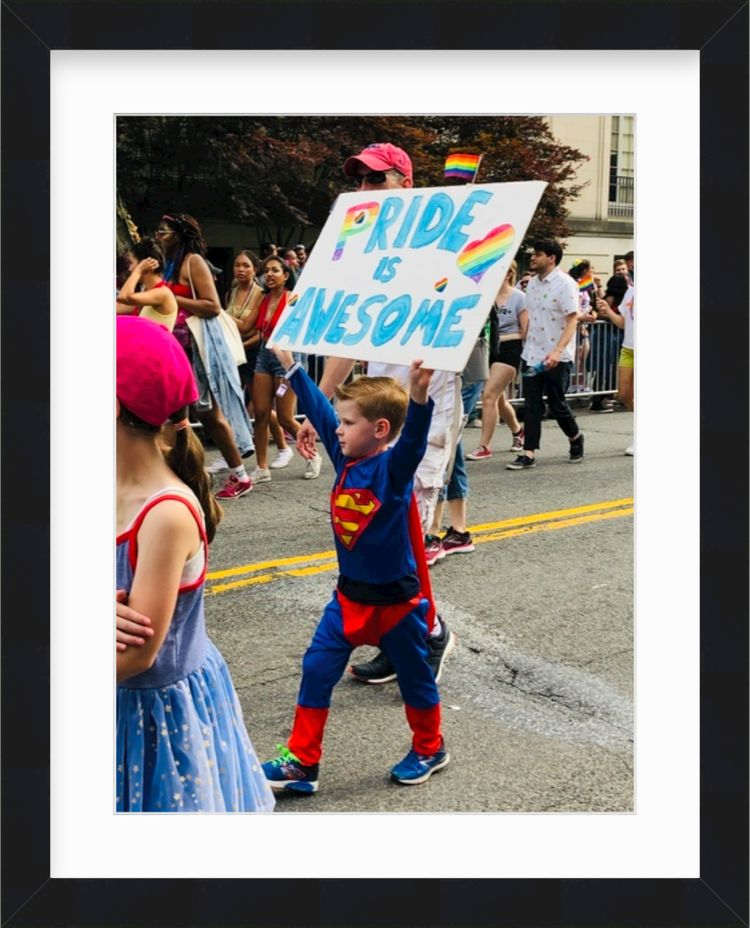 Boy in Superman costume holding pride sign in a black frame