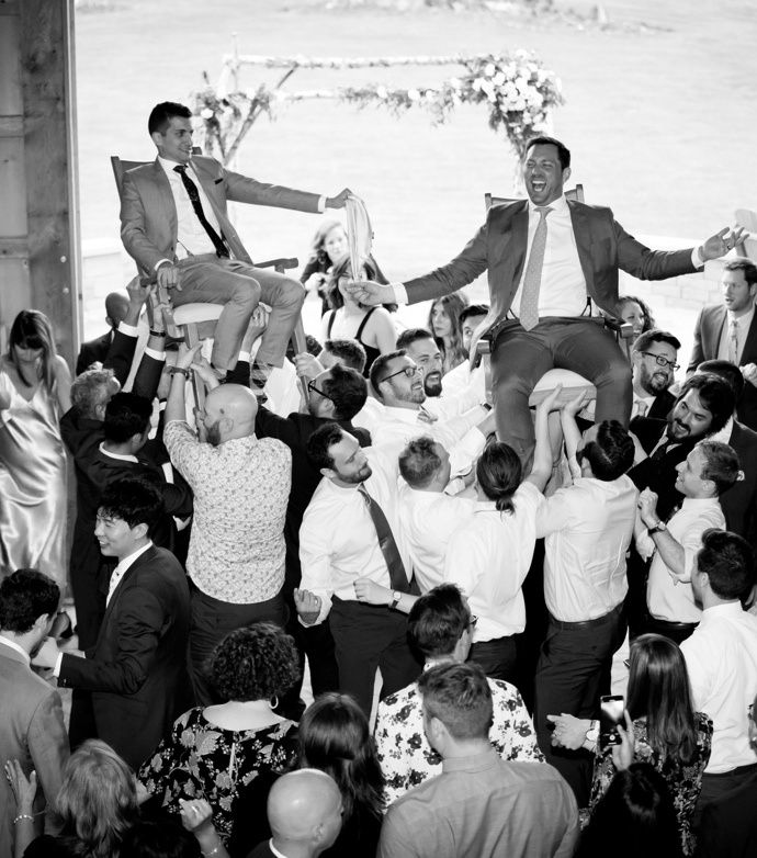 Couple hoisted in chairs at Jewish wedding