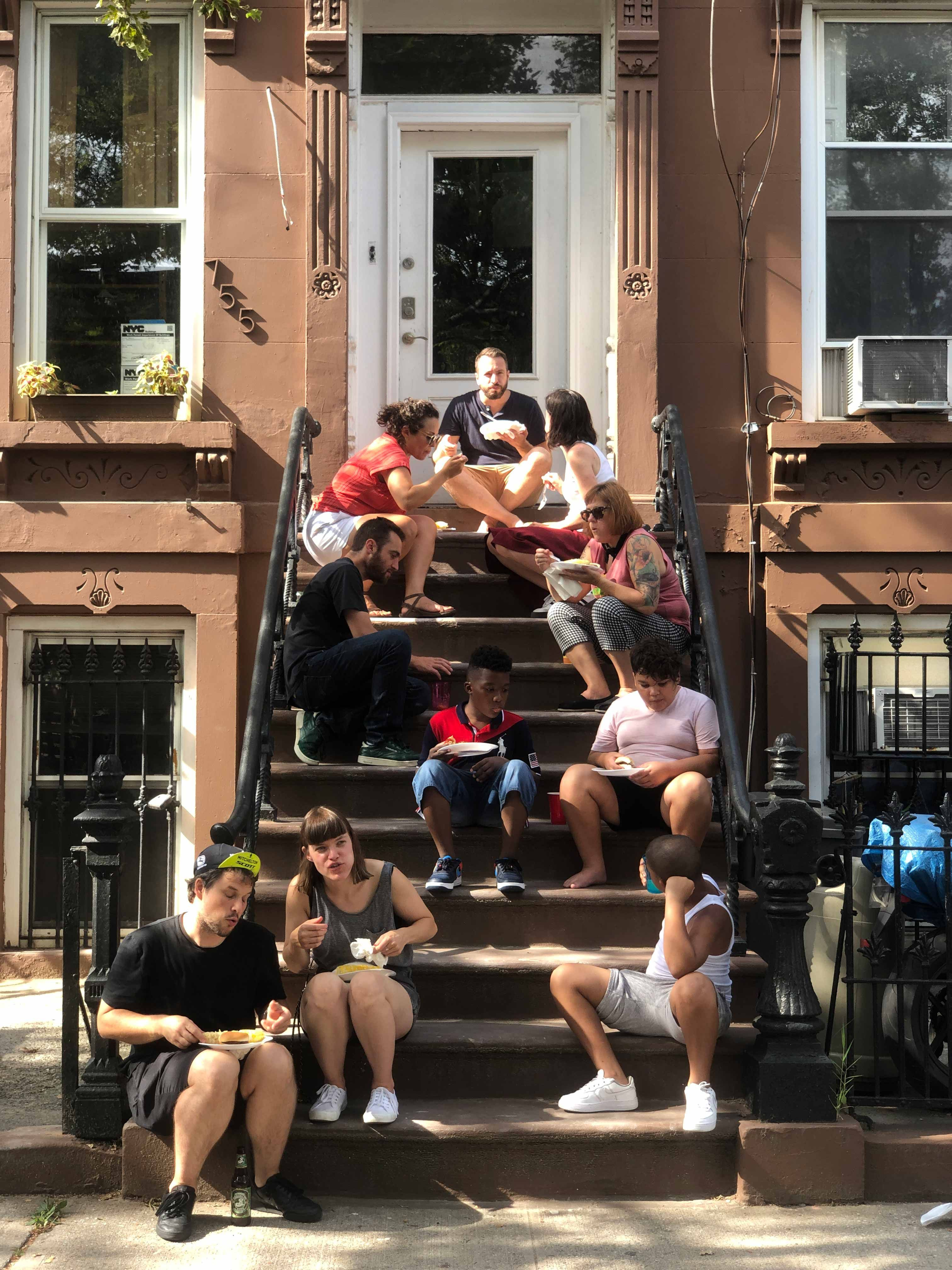 People eating on a Brooklyn stoop in a gold frame