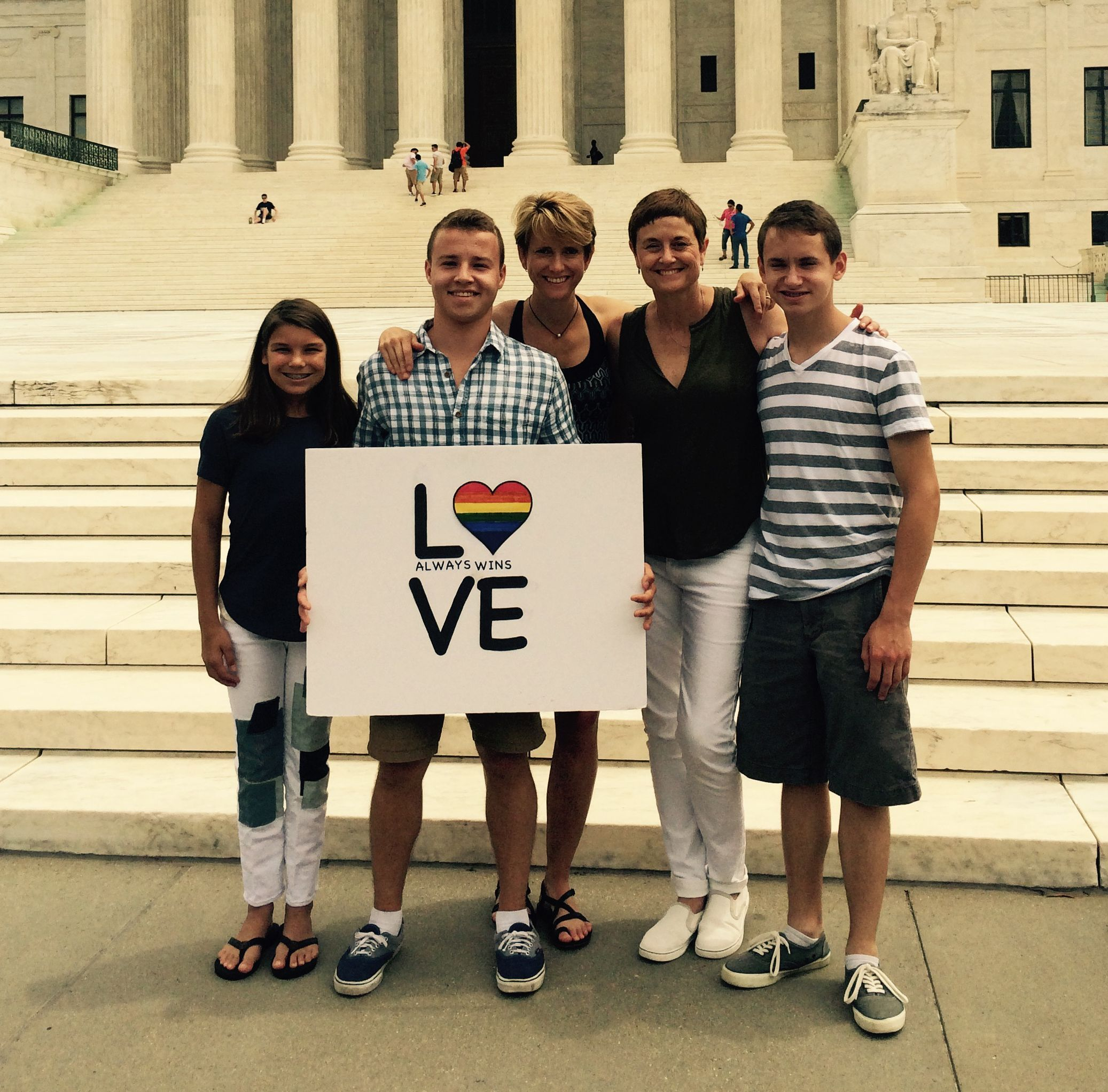 Family with pride sign in front of Supreme Court