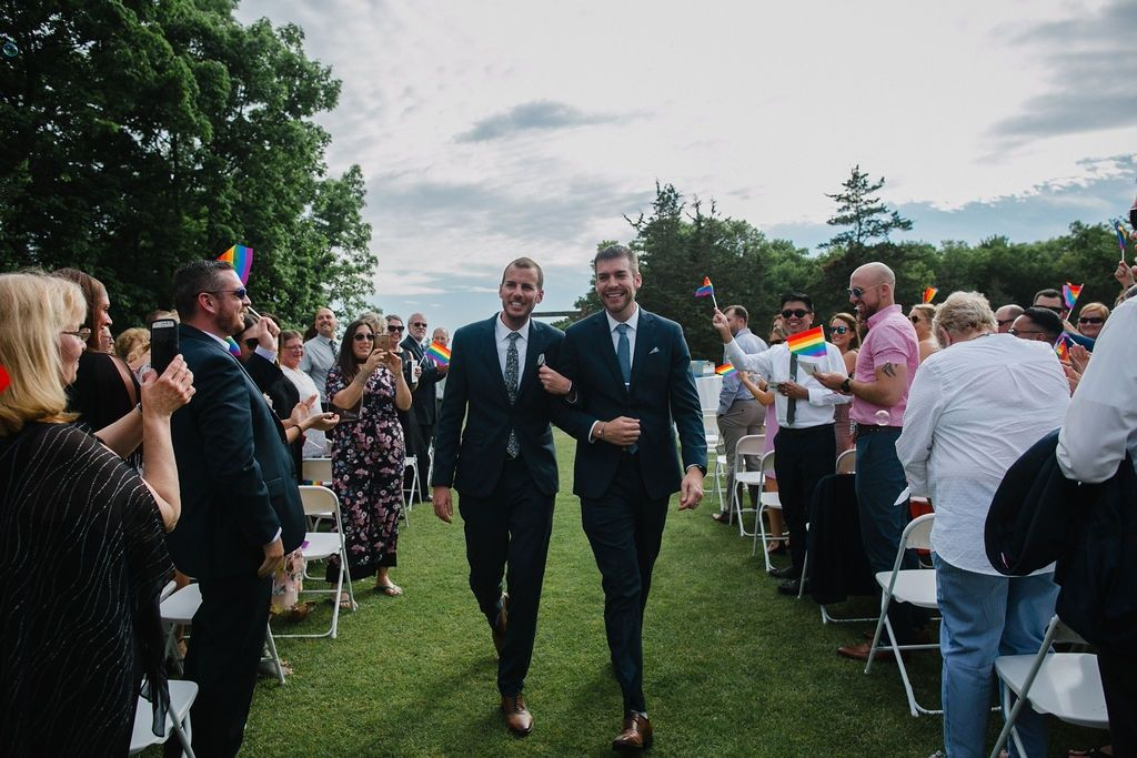 Two men wearing suits walk arm and arm after being wed as guests wave pride flags