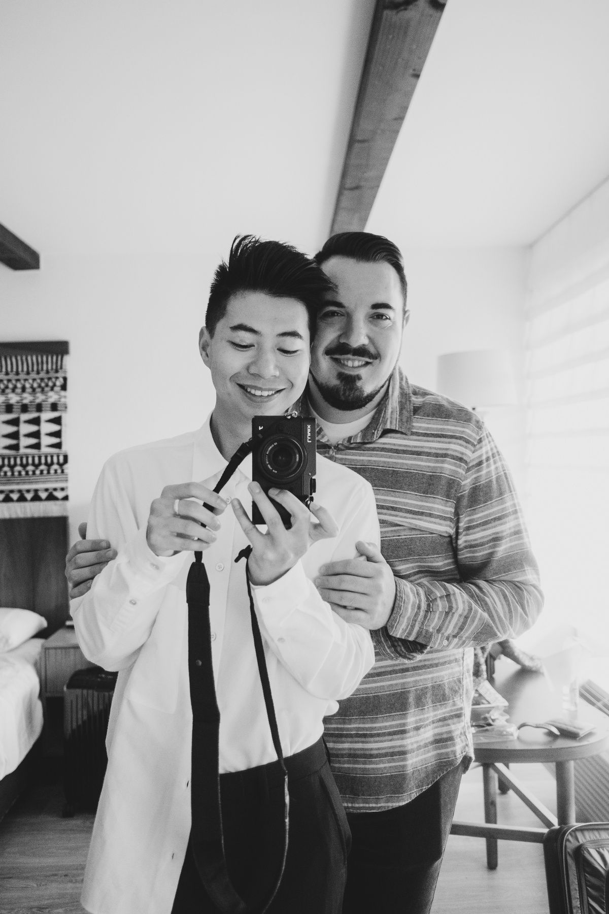 Black and white photo of two men taking a selfie in a mirror, one has their arms around the other