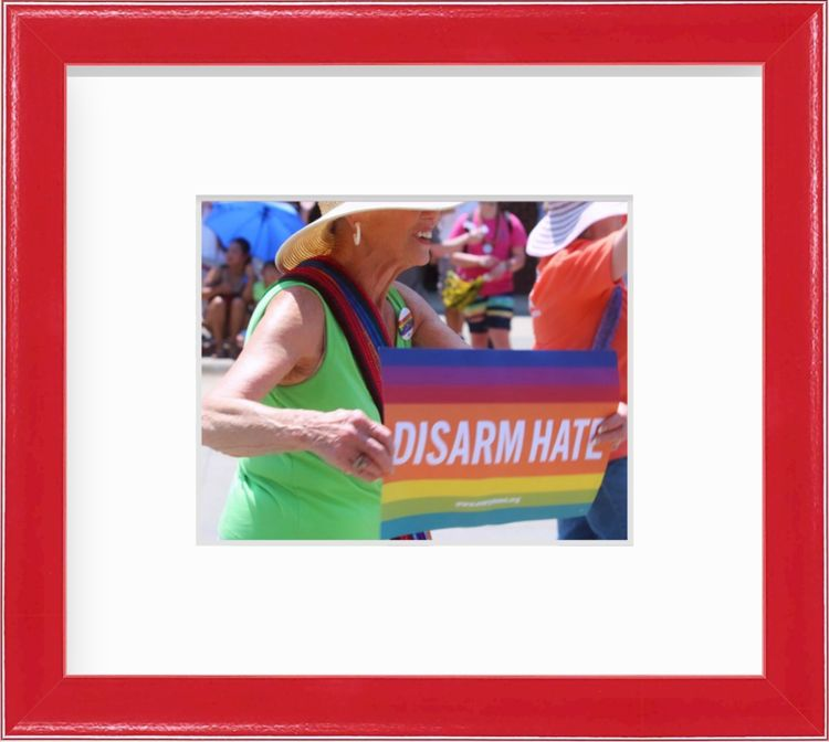 Woman holding rainbow sign that says disarm hate in a red frame