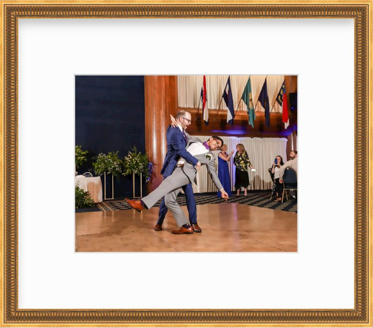 Two men dancing at wedding in a gold frame